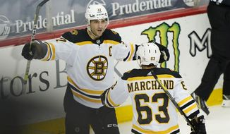 Boston Bruins center Patrice Bergeron (37) celebrates with left wing Brad Marchand (63) after scoring their second goal during the second period of an NHL hockey game against the New Jersey Devils, Monday, May 3, 2021, in Newark, N.J. Marchand got the assist on the goal. (AP Photo/Kathy Willens)