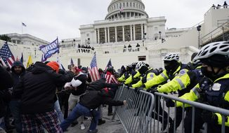 FILE - In this Jan. 6, 2021 file photo, Trump supporters try to break through a police barrier at the Capitol in Washington. With riot cases flooding into Washington's federal court, the Justice Department is under pressure to quickly resolve the least serious cases. (AP Photo/Julio Cortez, File)