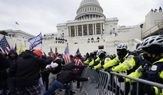 In this Jan. 6, 2021 file photo, Trump supporters try to break through a police barrier at the Capitol in Washington. With riot cases flooding into Washington's federal court, the Justice Department is under pressure to quickly resolve the least serious cases. (AP Photo/Julio Cortez, File)  **FILE**