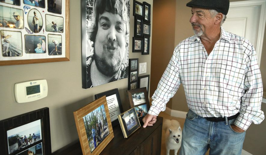Joe Kenney looks at the wall of his Southbank condominium which is decorated with photos from his son's life, Friday, April 16, 2021 in Jacksonville, Fla. Kenney's 30-year-old son Gary suffered from depression and committed suicide. The sense of helpless that Kenney felt when dealing with his son's depression led him to to fund Here Tomorrow, a Neptune Beach based group that tries to get immediate help for those who need it. (Bob Self/The Florida Times-Union via AP)