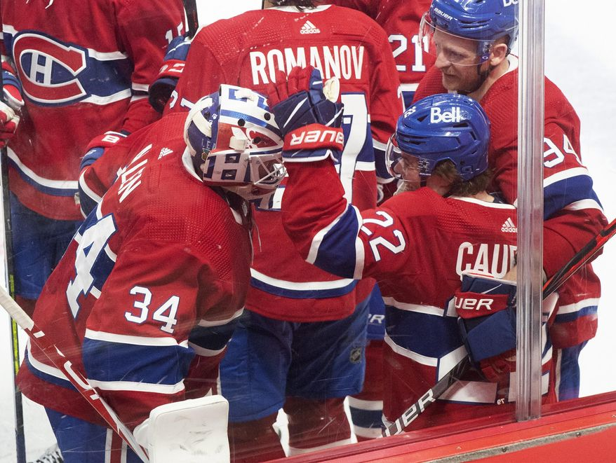 Montreal Canadiens' Cole Caufield (22) celebrates with teammates after scoring against the Toronto Maple Leafs during overtime