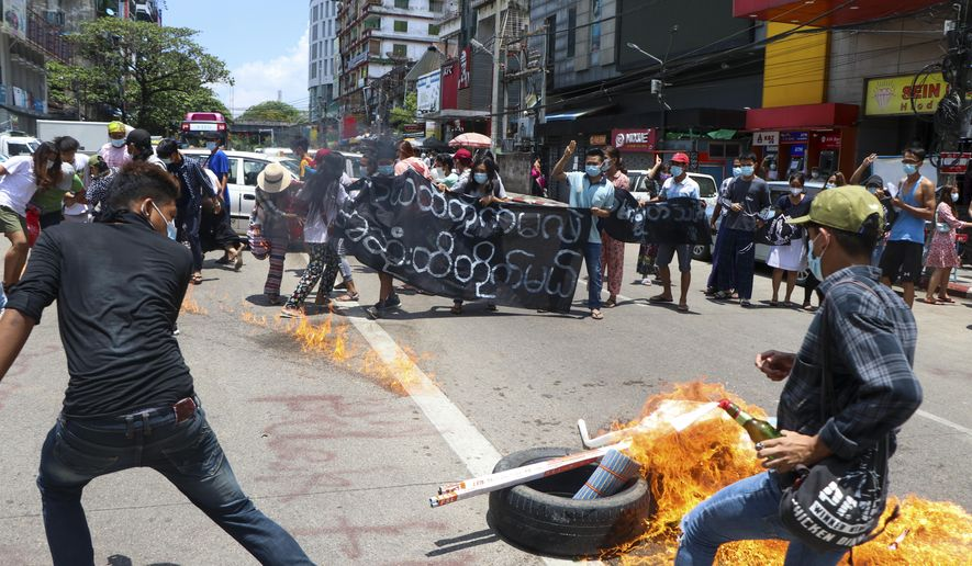 """Anti-coup protesters burn tires and chant slogans with banner read ''The Kamayut strike will be fight for to the end when we get victory"""" during the demonstration against the military coup in Kamayut township Yangon, Monday, May 3, 2021. (AP Photo)"""