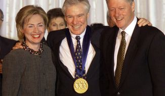 FILE - Dancer-choreographer Jacques d'Amboise poses with President Bill Clinton, right, and first lady Hillary Rodham Clinton at the White House after D'Amboise was presented with the National Medal of Arts Award on Nov. 5, 1998. D'Amboise, who grew up on the streets of upper Manhattan to become one of the world's premier classical dancers at New York City Ballet and spent the last four and a half decades providing free dance classes to city youth at his National Dance Institute, died Sunday, May 2, 2021. He was 86. His death was confirmed by Ellen Weinstein, director of the institute. (AP Photo/Doug Mills, File)