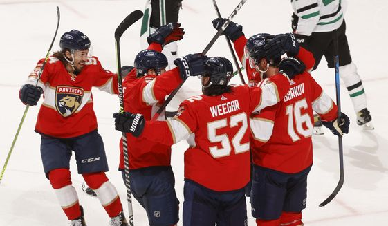 Teammates celebrate the game-winning goal by Florida Panthers center Aleksander Barkov (16) during the overtime period of an NHL hockey game, Monday, May 3, 2021, in Sunrise, Fla. (AP Photo/Joel Auerbach)