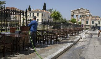 A man cleans with a water hose outside a traditional restaurant in front of the Roman Agora Gate, in Plaka, district of Athens, Friday, April 30, 2021. COVID-19 restrictions will be relaxed in Greece for Orthodox Easter on Sunday, allowing cafe and restaurant owners to serve customers outdoors. Tourism related services are expected to start operating on May 15. (AP Photo/Petros Giannakouris)