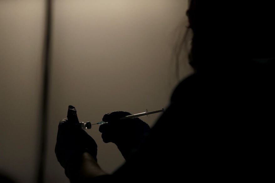 A volunteer vaccinator prepares to administer a dose of the Pfizer coronavirus vaccine at a vaccine centre in the Swaminarayan School in Neasden, north London, Saturday, May 1, 2021. (AP Photo/Matt Dunham)