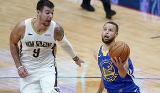 Golden State Warriors guard Stephen Curry (30) goes to the basket against New Orleans Pelicans center Willy Hernangomez (9) in the first half of an NBA basketball game in New Orleans, Monday, May 3, 2021. (AP Photo/Gerald Herbert)