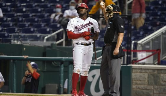 Washington Nationals' Josh Bell talks with home plate umpire Jeff Nelson after batting during the inning of baseball game against the Atlanta Braves at Nationals Park, Tuesday, May 4, 2021, in Washington. (AP Photo/Alex Brandon)