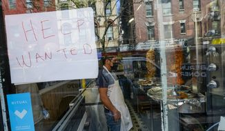 A Help Wanted sign hangs in the window of a restaurant in the Greenwich Village neighborhood of Manhattan in New York, Tuesday, May 4, 2021 Some restaurants in New York City are starting to hire employees now that they can increase their indoor dining to 75% of capacity starting May 7. (AP Photo/Mary Altaffer)