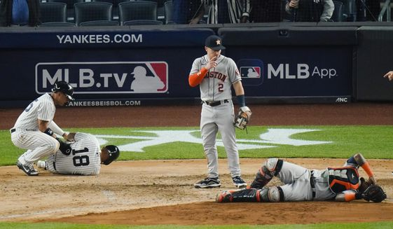 Houston Astros' Alex Bregman, center, watches as New York Yankees' Rougned Odor, left, and Houston Astros catcher Martin Maldonado, right, react to being injured on a play at home plate during the sixth inning of a baseball game Tuesday, May 4, 2021, in New York. (AP Photo/Frank Franklin II)