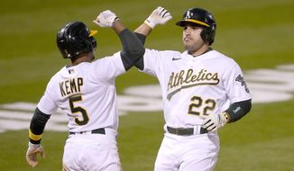 Oakland Athletics' Ramon Laureano (22) gets a forearm-bash with his teammates Tony Kemp (5) after hitting a two-run home run against the Toronto Blue Jays during the fifth inning of a baseball game in Oakland, Calif., on Monday, May 3, 2021. (AP Photo/Tony Avelar)