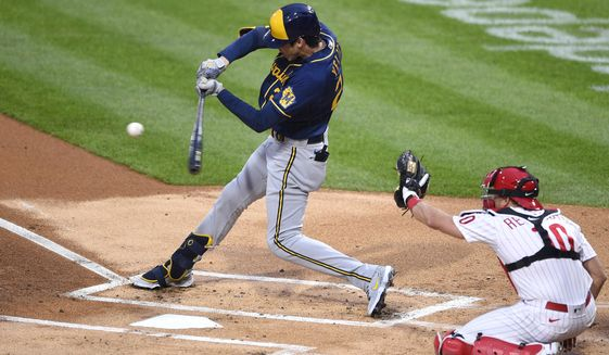 Milwaukee Brewers' Christian Yelich, left, hits a single during the first inning of a baseball game in front of Philadelphia Phillies' J.T. Realmuto (10), Monday, May 3, 2021, in Philadelphia. (AP Photo/Derik Hamilton)