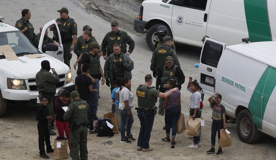 In this Dec. 10, 2018, photo, a girl waves to a young man watching from Mexican territory who said he was her cousin, as a group of Honduran asylum seekers is taken into custody by U.S. Border Patrol agents after the group crossed the U.S. border wall into San Diego, seen from Tijuana, Mexico. San Diego County has approved a plan to provide attorneys to immigrants facing deportation proceedings. The Board of Supervisors on Tuesday, May 4, 2021 approved a $5 million, one-year pilot program. It would provide lawyers for free to those detained at Otay Mesa Detention Center, the local federal immigration detention facility. San Diego will be the first southern border county in the U.S. to provide such legal representation. (AP Photo/Rebecca Blackwell) **FILE**
