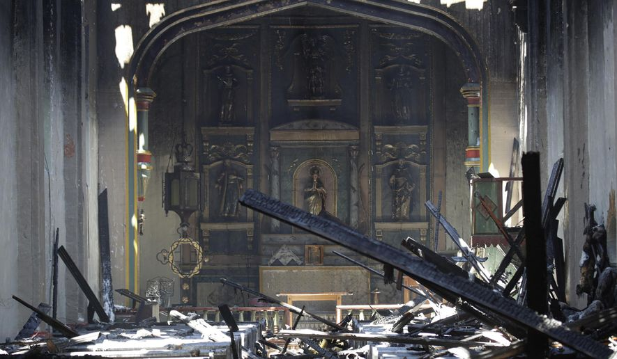 FILE - In this Saturday, July 11, 2020, file photo, the interior of the San Gabriel Mission is seen in the aftermath of an early morning fire in San Gabriel, Calif.  A fire that gutted much of the historic Catholic church in Southern California last year was intentionally set by a 57-year-old man, prosecutors said Tuesday, May 4, 2021. John David Corey faces multiple felony counts including arson of an inhabited structure, the Los Angeles County District Attorney's Office said in a statement  (AP Photo/Marcio Jose Sanchez, File)