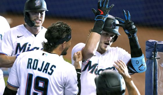 Miami Marlins' Brian Anderson (15) celebrates with Miguel Rojas (19) after hitting a three-run home run during the first inning of a baseball game against the Arizona Diamondbacks, Tuesday, May 4, 2021, in Miami. (AP Photo/Lynne Sladky)