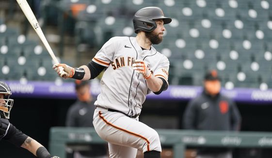 San Francisco Giants' Brandon Belt follows the flight of his single off Colorado Rockies relief pitcher Jhoulys Chacin in the fourth inning of game one of a baseball doubleheader Tuesday, May 4, 2021, in Denver. (AP Photo/David Zalubowski)
