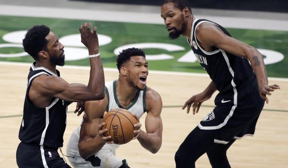 Milwaukee Bucks' Giannis Antetokounmpo, middle, drives to the basket between Brooklyn Nets' Jeff Green, left, and Kevin Durant, right, during the first half of an NBA basketball game Tuesday, May 4, 2021, in Milwaukee. (AP Photo/Aaron Gash)