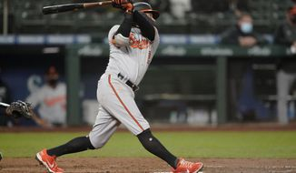 Baltimore Orioles' Freddy Galvis follows through on a two-run home run during the eigth inning of a baseball game against the Seattle Mariners, Monday, May 3, 2021, in Seattle. (AP Photo/Ted S. Warren)