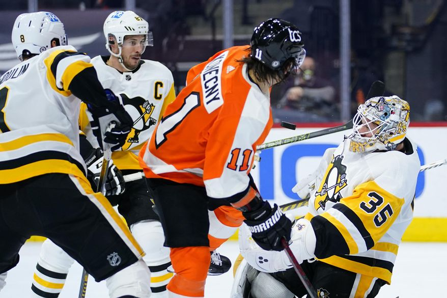 Pittsburgh Penguins' Tristan Jarry (35) blocks a shot as Sidney Crosby (87) Brian Dumoulin (8) and Philadelphia Flyers' Travis Konecny (11) look on during the third period of an NHL hockey game, Tuesday, May 4, 2021, in Philadelphia. (AP Photo/Matt Slocum)