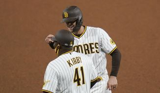 San Diego Padres' Wil Myers, right, reacts after hitting a single as first base coach Wayne Kirby (41) looks on during the seventh inning of a baseball game against the Pittsburgh Pirates, Monday, May 3, 2021, in San Diego. (AP Photo/Gregory Bull)
