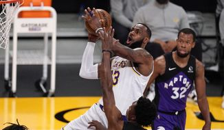 Los Angeles Lakers forward LeBron James, upper left, shoots as Toronto Raptors forward Stanley Johnson, lower left, and guard Rodney Hood defend during the first half of an NBA basketball game Sunday, May 2, 2021, in Los Angeles. (AP Photo/Mark J. Terrill) **FILE**