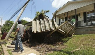 A Tupelo resident walks by a home on North Green Street on Monday, May 3, 2021 that had a tree fall and it roots tear out the decking and stairway to the home after a tornado passed through the city Sunday night. (Adam Robison/The Northeast Mississippi Daily Journal via AP)