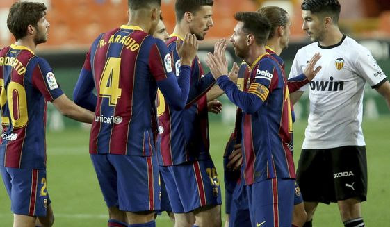 Barcelona's Lionel Messi celebrates with team mates the victory of his team at the end of a Spanish La Liga soccer match against Valencia at the Mestalla stadium in Valencia, Spain, Sunday, May 2, 2021. (AP Photo/Alberto Saiz)
