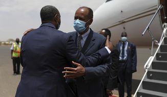 President of the Sudanese Transitional Council General Abdel Fattah al-Burhan, left, greets Eritrean President Isaias Afwerki at the Khartoum airport in Khartoum, Sudan, Tuesday, May 4, 2021. Eritrea's president arrived in Khartoum on Tuesday for talks with Sudanese officials amid tensions between the two countries over the Tigray conflict on Sudan's border. (AP Photo/Marwan Ali)