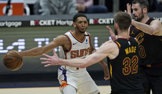 Phoenix Suns' Cameron Payne, left, passes around Cleveland Cavaliers' Dean Wade and Kevin Love in the first half of an NBA basketball game, Tuesday, May 4, 2021, in Cleveland. (AP Photo/Tony Dejak)