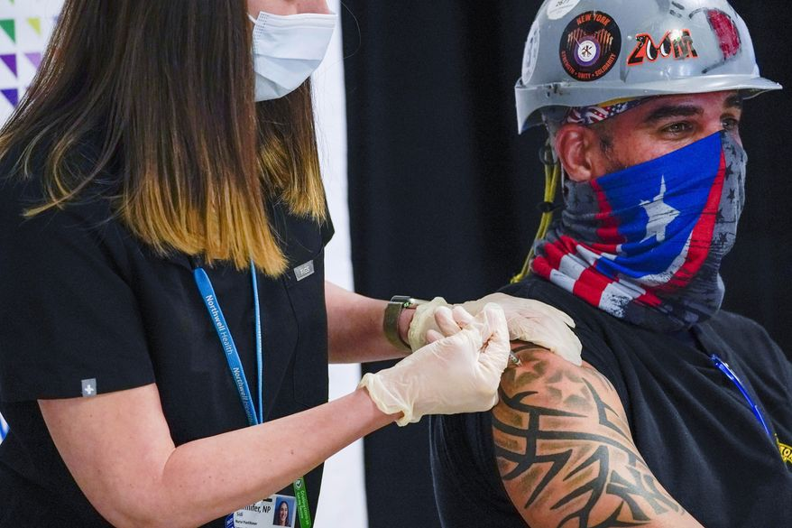 In this April 14, 2021 file photo, a Northwell Health nurse injects Local 28 Sheet Metal Worker Demetrius Buttelman with the first dose of the Pfizer vaccine during a news conference, at the Belmont Park in Elmont, N.Y. The state recorded 43,000 new cases in the week that ended Saturday, April 17, 2021. That's the lowest number in a seven-day period since Thanksgiving. (AP Photo/Mary Altaffer, Pool, File)