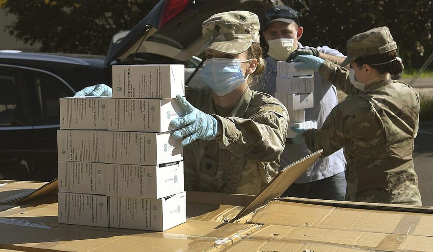 """FILE - In this Wednesday, May 27, 2020, file photo, Oregon National Guard's Ashley Smallwood, of Springfield, Ore., counts out boxes of face masks to be given to Willamette Valley farmers while participating in a distribution event at the Oregon State University Extension Service-Linn County office in Tangent, Ore. Oregon adopted a controversial rule on Tuesday, May 4, 2021 that indefinitely extends coronavirus mask and social distancing requirements in all businesses in the state. State officials say the rule, which garnered thousands of public comments, will be in place until it is """"no longer necessary to address the effects of the pandemic in the workplace."""" (Mark Ylen/Albany Democrat-Herald via AP, file)"""