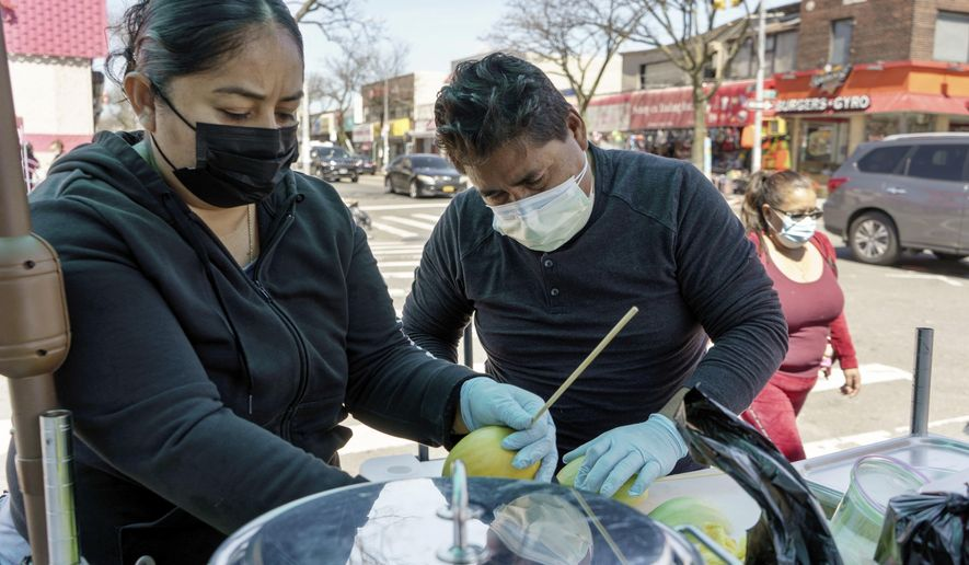 Ruth Palacios and Arturo Xelo, a married couple from Mexico, work at their fruit stand in the Corona neighborhood of the Queens borough of New York on Tuesday, April 13, 2021. They worked seven days a week for months disinfecting COVID-19 patient rooms at the Memorial Sloan Kettering Cancer Center in New York City, but weren't paid overtime Palacios says. The couple filed a federal lawsuit against the contractor that hired them, alleging their pay was cut without their knowledge from $15 an hour to $12.25. They're now selling fruit to make ends meet. (AP Photo/Marshall Ritzel)