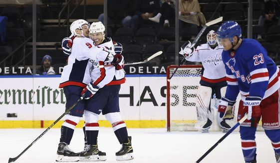 Washington Capitals' T.J. Oshie (77) is is hugged by Dmitry Orlov (9) after his third goal of the night aganist the New York Rangers in an NHL hockey game Wednesday, May 5, 2021, in New York. (Bruce Bennett/Pool Photo via AP)