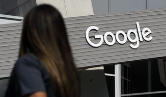 In this Sept. 24, 2019, file photo, a woman walks below a Google sign on the campus in Mountain View, Calif. On Wednesday, May 5, 2021, Google said that it expects about 20% of its workforce to still work remotely after the coronavirus pandemic. In addition, some 60% will work a hybrid schedule that includes about three days in the office and two days wherever the employees work best. (AP Photo/Jeff Chiu, File)