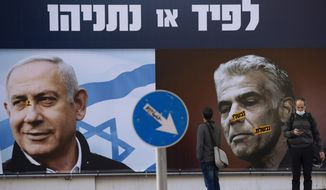 In this March 14, 2021, file photo, people stand in front of an election campaign billboard for the Likud party showing a portrait of its leader Prime Minister Benjamin Netanyahu, left, and opposition party leader Yair Lapid, in Ramat Gan, Israel. Israeli President Reuven Rivlin has tapped Lapid to form a new government, a step that could lead to the end of Netanyahu's lengthy rule. (AP Photo/Oded Balilty, File)