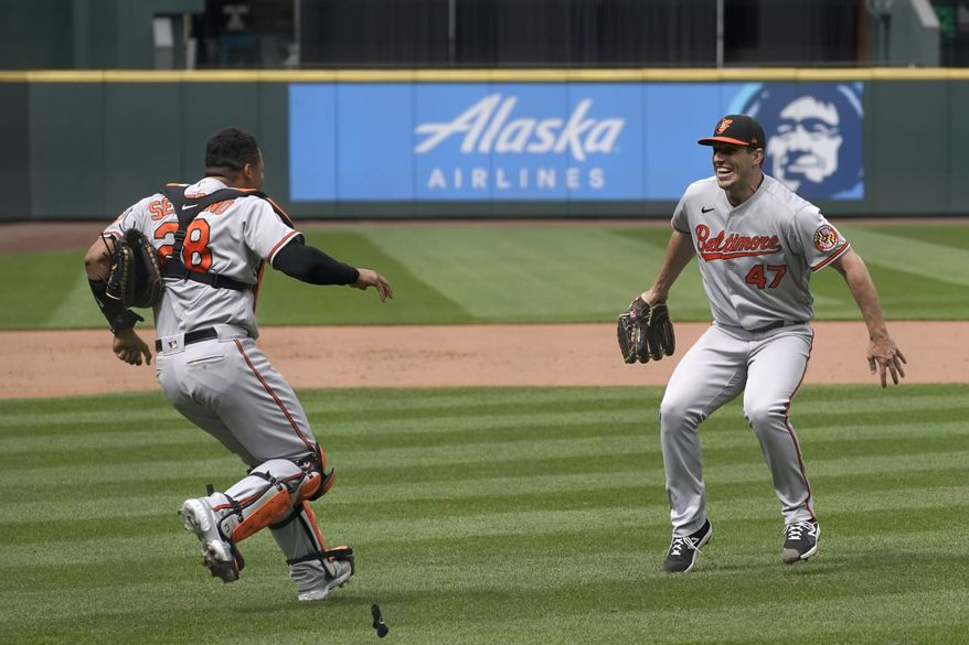 Baltimore Orioles starting pitcher John Means, right, celebrates with catcher Pedro Severino after Means threw a no-hitter baseball game against the Seattle Mariners, Wednesday, May 5, 2021, in Seattle. The Orioles won 6-0. (AP Photo/Ted S. Warren)