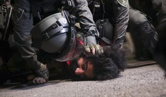 Israeli police officers detain a Palestinian demonstrator during a protest against the planned evictions of Palestinian families in the Sheikh Jarrah neighborhood of east Jerusalem, Tuesday, May 4, 2021. (AP Photo/Mahmoud Illean)