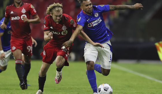 Walter Montoya of Mexico's Cruz Azul, right, and Jacob Shaffelburg of Canada's Toronto FC fight for the ball during CONCACAF Champions League quarterfinal second leg soccer match at Azteca stadium in Mexico City, Tuesday, May 4, 2021. (AP Photo/Fernando Llano)