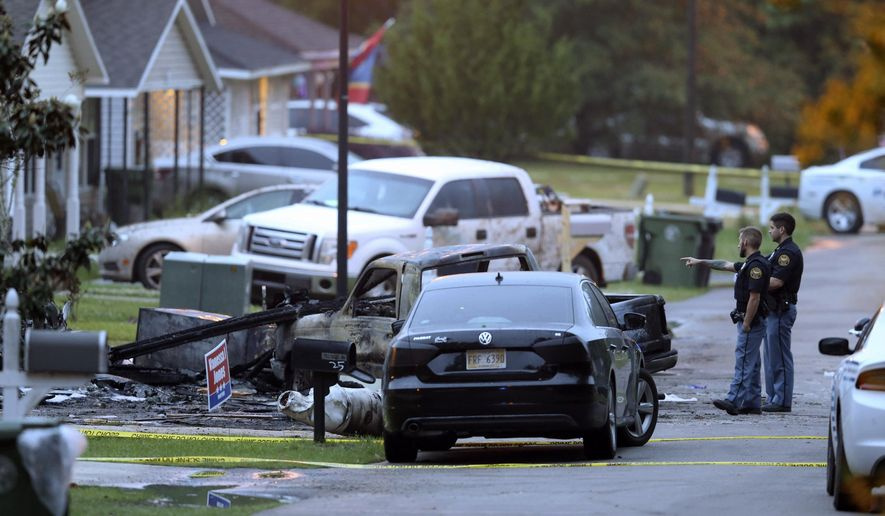 Hattiesburg police surround a burned automobile and a damaged home after a small plane crashed late Tuesday night in Hattiesburg, Miss., Wednesday May 5, 2021.   Emergency officials in Mississippi say multiple people were killed when the small plane crashed into a home. (AP Photo/Chuck Cook)