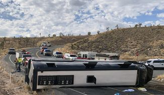 This photo provided by the Mohave County Sheriff's Office shows a  Las Vegas-based tour bus that crashed, Jan. 22, 2021, in Dolan Springs, Ariz. A crash report on the tour bus that flipped on the way to the west end of the Grand Canyon, killing one passenger, doesn't draw any conclusion about the cause but points to speed as a factor. Four dozen people from across the country were on the bus operated by Comedy On Deck Tours when it veered into a dirt embankment, over ruts and rocks, and hit Joshua trees Jan. 22. (Mohave County Sheriff's Office via AP)