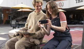 """This image released by IFC Films shows Andrew Garfield, left, and Maya Hawke in a scene from """"Mainstream,"""" a film by Gia Coppola. (Beth Dubber/IFC Films via AP)"""