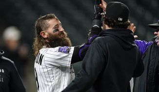 Teammates congratuate Colorado Rockies' Charlie Blackmon, left, after he hit a three-run, walkoff home run off San Francisco Giants relief pitcher Camilo Doval in the seventh inning of game two of a baseball doubleheader Tuesday, May 4, 2021, in Denver. The Rockies won the nightcap by score of 8-6.(AP Photo/David Zalubowski)