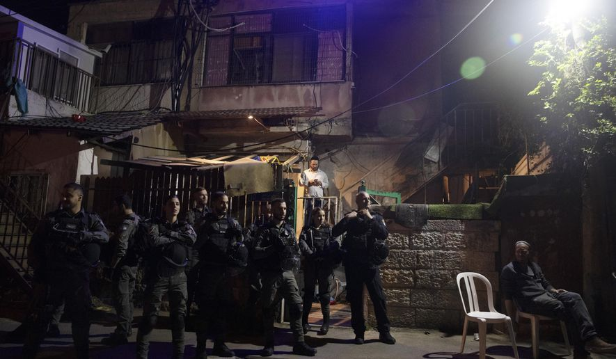 Israeli police stand guard in front of a Palestinian home occupied by settlers during a protest on the eve of a court verdict that may forcibly evict Palestinian families from their homes in the Sheikh Jarrah neighborhood of Jerusalem, Wednesday, May 5, 2021. Several Palestinian families in Sheikh Jarrah have been embroiled in a long-running legal battle with Israeli settler groups trying to acquire property in the neighborhood near Jerusalem's famed Old City. (AP Photo/Maya Alleruzzo)