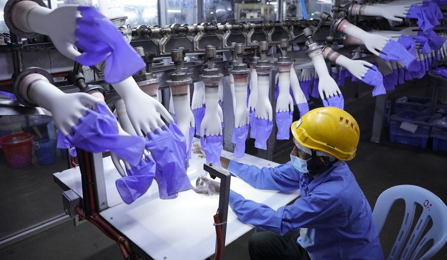 FILE - In this Aug. 26, 2020, file photo, a worker inspects disposable gloves at the Top Glove factory in Shah Alam on the outskirts of Kuala Lumpur, Malaysia. Malaysia's Top Glove Corp., the world's largest rubber glove maker, said Wednesday, May 5, 2021, it hopes to swiftly end a U.S. ban on its products due to allegations of forced labor after one of its shipment was seized at a U.S. port. (AP Photo/Vincent Thian, File)