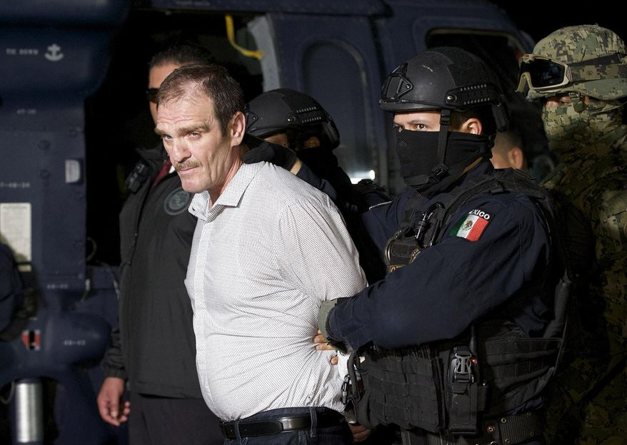 """FILE - In this June 15, 2016 file photo provided by the Mexican Attorney General's Office, Hector """"El Guero"""" Palma, or """"Blondie,"""" one of the founders of the Sinaloa Cartel, is escorted in handcuffs from a helicopter at a federal hangar in Mexico City, after serving almost a decade in a U.S. prison and transported to another maximum-security lockup to await trial for two murders. (Mexico's Attorney General's Office via AP, File)"""