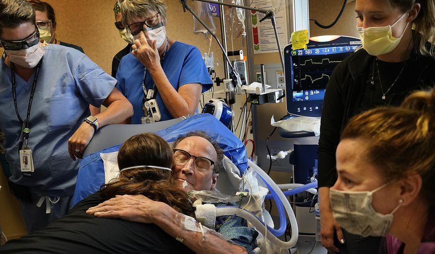 In this May 3, 2021, file photo, Hennepin County Medical Center patient John Grubb, of St. Michael, hugs and says goodbye to several of his caregivers as his wife, Kelly, lower right, looks on before he is discharged from the hospital in Minneapolis, after spending 81 days on the ECMO heart-lung bypass machine, which has been the treatment of last resort in COVID-19 care. (David Joles/Star Tribune via AP, File)