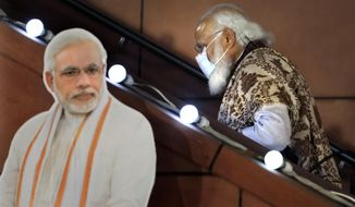 FILE - In this Nov. 11 2020, file photo, Indian Prime Minister Narendra Modi leaves after a function at the Bharatiya Janata Party headquarters following a state election in New Delhi, India. Despite clear signs that India was being swamped by another surge of coronavirus infections, Modi refused to cancel campaign rallies, a major Hindu festival and cricket matches with spectators. The crisis has badly dented Modi's carefully cultivated image as an able technocrat.  (AP Photo/Manish Swarup, File)