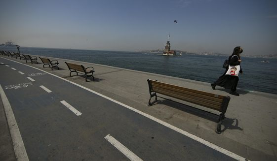 Backdropped by the Maiden's Tower a woman walks on a nearly deserted promenade by the Bosphorus Strait in Istanbul, Friday, April 30, 2021, on the first day of a tight lockdown to help protect from the spread of the coronavirus. Turkish security forces on Friday patrolled main streets and set up checkpoints at entry and exits points of cities, to enforce Turkey's strictest COVID-19 lockdown to date. Still, many people were on the move as the government, desperate not to shut down the economy completely, kept some sectors exempt from the restrictions. (AP Photo/Emrah Gurel)