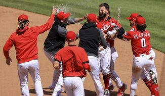 Cincinnati Reds' Jesse Winker, back right, celebrates with teammates after hitting an RBI walk-off single during the tenth inning of a baseball game against the Chicago White Sox in Cincinnati, Wednesday, May 5, 2021. The Reds won 1-0. (AP Photo/Aaron Doster)