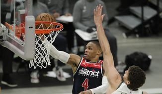 Washington Wizards' Russell Westbrook (4) goes to the hoop against Milwaukee Bucks' Brook Lopez during the first half of an NBA basketball game Wednesday, May 5, 2021, in Milwaukee. (AP Photo/Aaron Gash)
